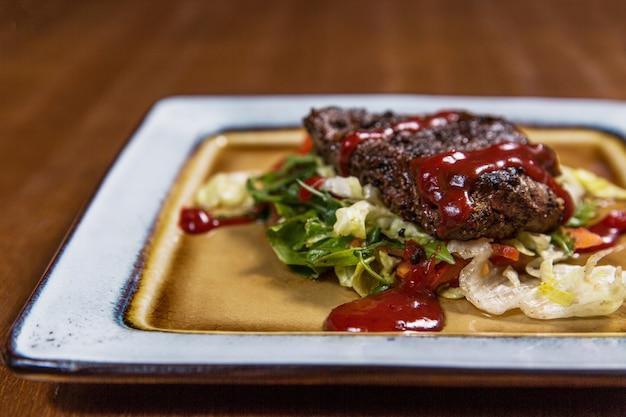 Gros steak de viande avec des légumes et des sauces dans une assiette carrée sur une table en bois dans un restaurant de luxe