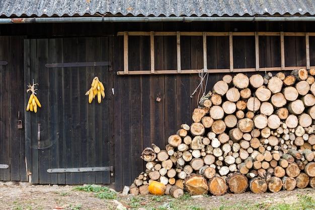 Gros tas soigneusement empilé de bûches de bois de feu haché préparé pour l'hiver au mur de la grange en bois vintage