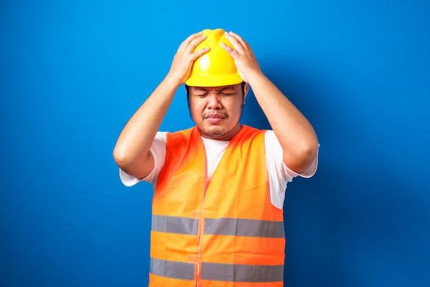 Gros travailleur de la construction asiatique portant un casque de sécurité stressé avec la main sur la tête