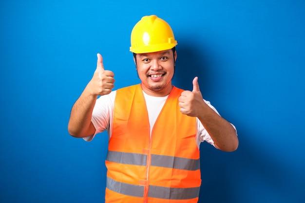 Gros Travailleur De La Construction Asiatique Portant Un Gilet De Sécurité Orange Et Un Casque Montrant Le Pouce Vers Le Haut En Souriant Photo Premium