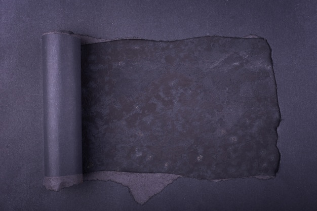 Gros trou dans le papier noir. déchiré. fond en béton. abstrait.