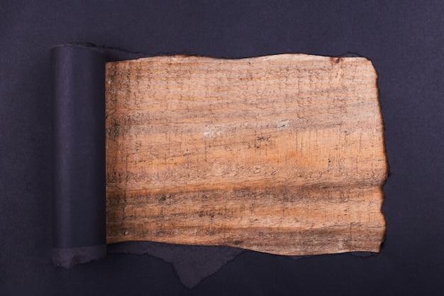 Gros trou dans le papier noir. déchiré. fond en bois. abstrait.