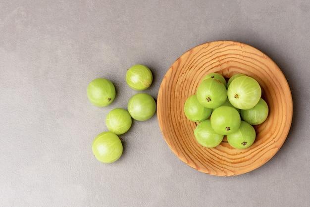 Groseille à maquereau indienne ou phyllanthus emblica fruits sur fond céramique.vue de dessus, mise à plat