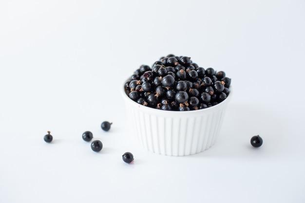 Groseilles mûres ou myrtilles dans une petite tasse blanche sur blanc