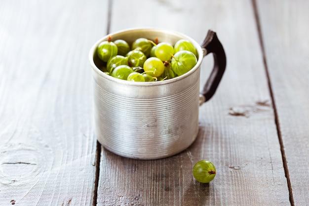 Groseilles vertes dans une tasse en aluminium