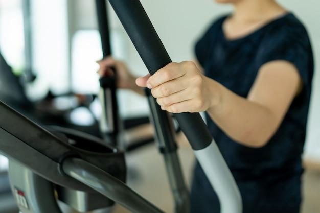 Grosse femme asiatique à l'aide de machines d'exercice dans une salle de sport intérieure, sport, portrait de femme avec espace de copie.