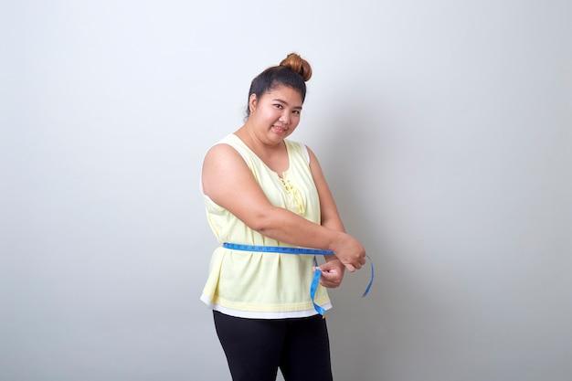 Grosse femme asiatique mesurant