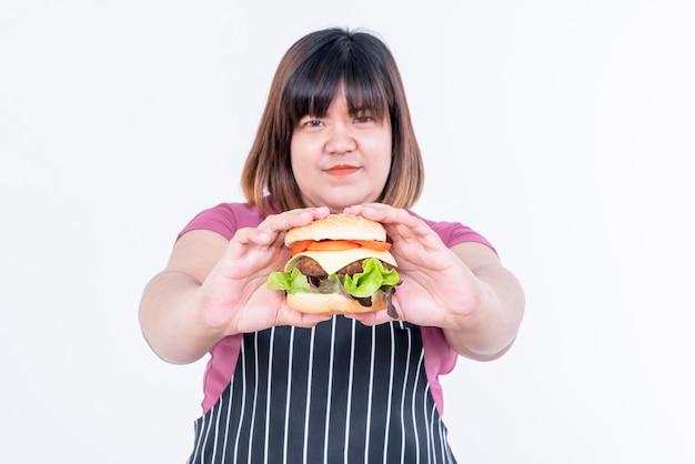 Grosse femme asiatique montre des hamburgers qui tenaient dans ses mains