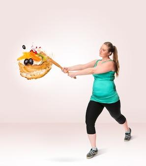 Une grosse femme brisant un gâteau sucré avec une chauve-souris. aliments malsains. le concept de régime et de mode de vie sain pour la grosse femme