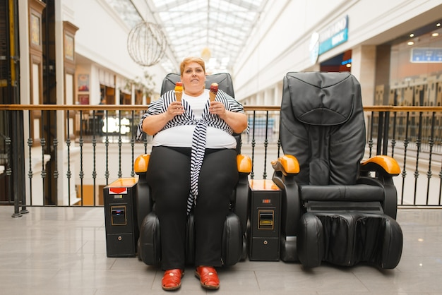 Grosse femme avec de la crème glacée assise sur une chaise de massage dans un centre commercial. une femme en surpoids pose dans un fauteuil en cuir dans un centre commercial, problème d'obésité