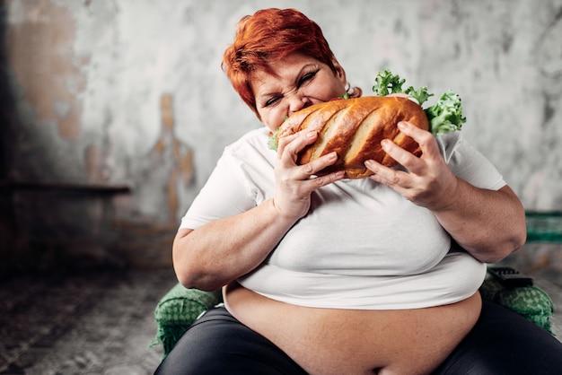 Grosse femme est assise sur une chaise et mange un sandwich, boulimique