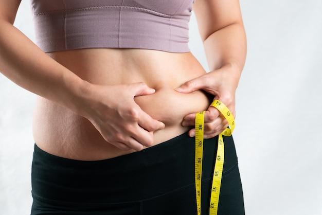 Grosse femme, gros ventre, joufflu, main de femme obèse tenant la graisse du ventre excessive avec du ruban à mesurer, concept de mode de vie de femme