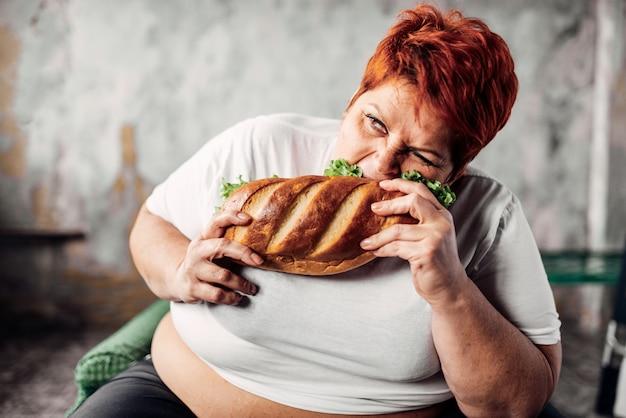 Grosse femme mange sandwich, surpoids et boulimique