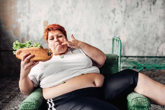 Grosse femme mange un sandwich, en surpoids, gras