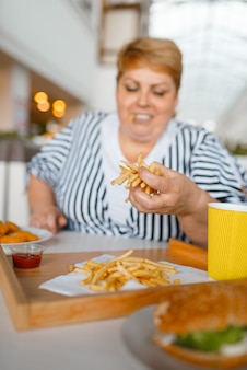 Grosse femme mangeant des aliments riches en calories au centre commercial