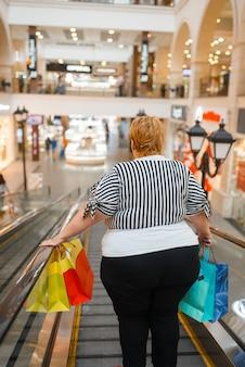 Grosse femme avec des sacs sur l'escalator