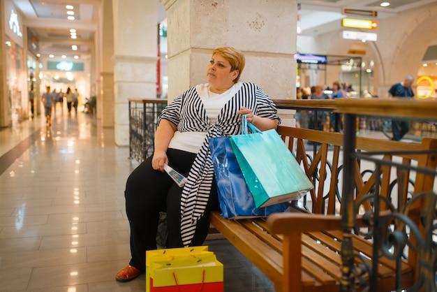 Grosse femme avec des sacs à provisions assis sur le banc dans le centre commercial. personne de sexe féminin en surpoids dans un supermarché, problème d'obésité