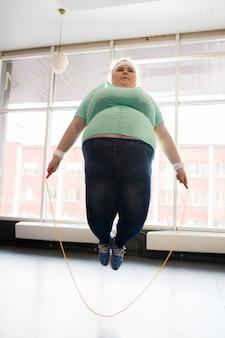 Grosse femme sautant avec une corde