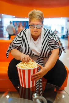 Grosse femme tenant du pop-corn dans la salle de cinéma