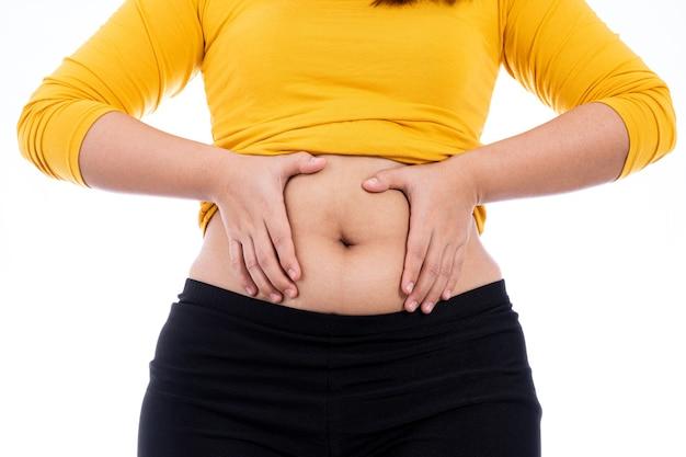 Grosse femme tenant un ventre gras excessif isolé blanc.