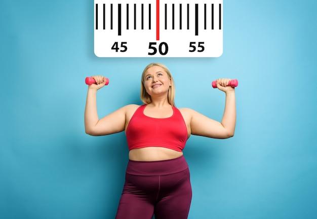 Grosse fille fait de la gym à la maison avec une expression satisfaite parce qu'elle diminue son poids fond cyan