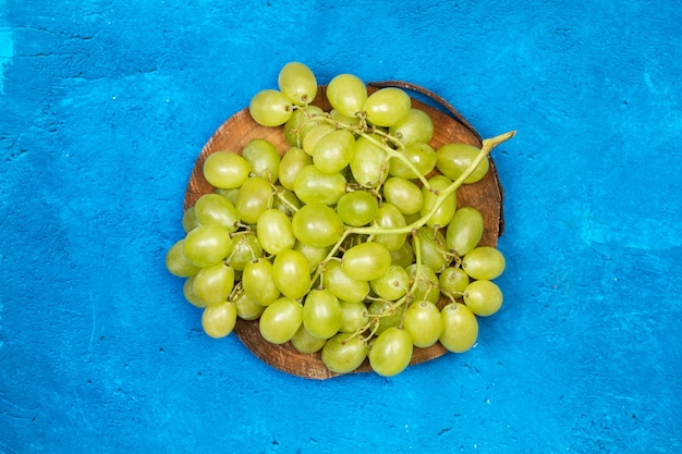 Une grosse grappe de raisin vert sur un tronc d'arbre et sur fond bleu