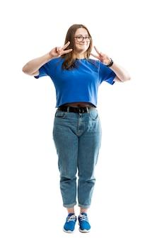 Une grosse jeune femme souriante en t-shirt bleu et jeans se dresse et montre le signe de la victoire