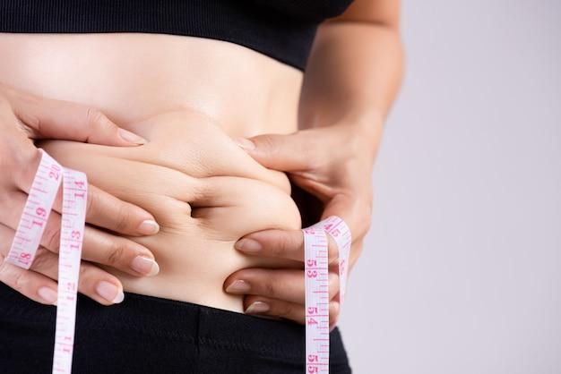 Grosse main de femme tenant la graisse du ventre excessive avec un ruban à mesurer.