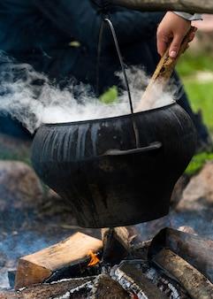 Grosse marmite noire en feu à l'extérieur.