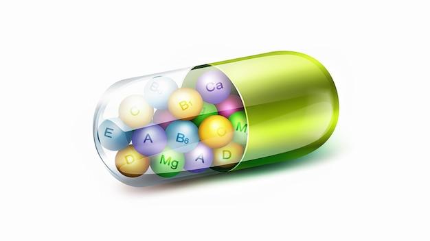 Grosse pilule verte avec des boules de vitamines à l'intérieur sur fond blanc