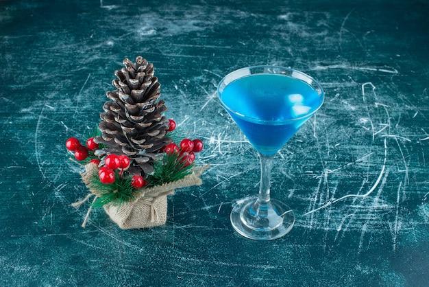 Une grosse pomme de pin de noël avec une tasse en verre de boisson bleue.