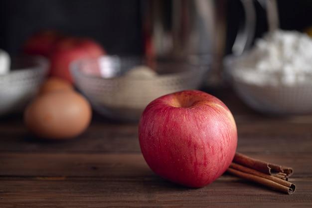 Grosse pomme rouge avec des bâtons de cannelle et des ingrédients de base pour la cuisson de la tarte aux pommes sur fond brun foncé