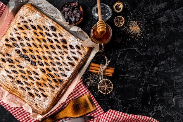 Grosse tarte maison sucrée avec des baies sur une surface noire