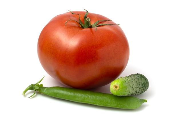 Une grosse tomate, un petit concombre et une cosse de jeunes pois verts. légumes frais isolés sur fond blanc.