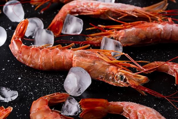 Grosses crevettes crues surgelées sur fond noir