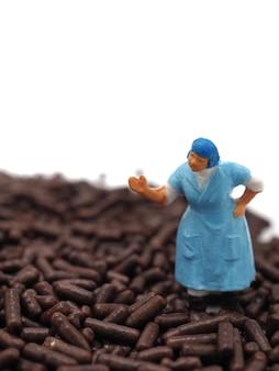 Grosses femmes miniatures sur pépites de chocolat sur fond blanc. concept de perte de régime, de graisse et de poids.
