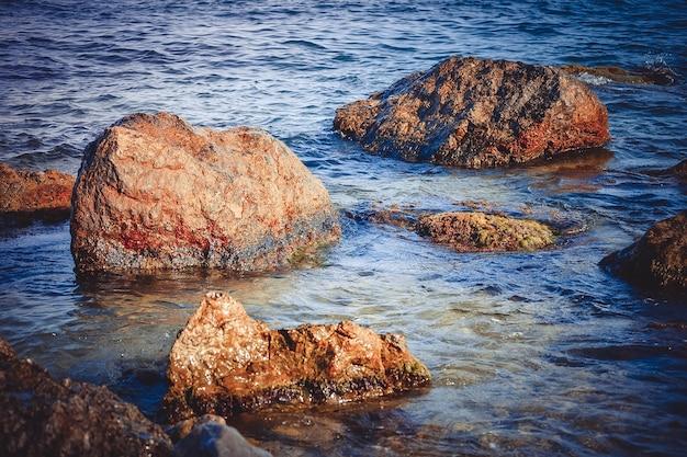 Grosses pierres humides dans l'eau par une journée ensoleillée