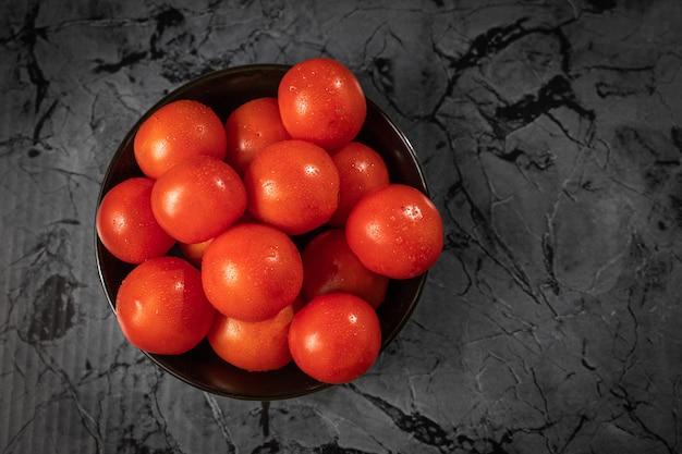 Grosses tomates rouges sur une plaque noire, sur une table en granit