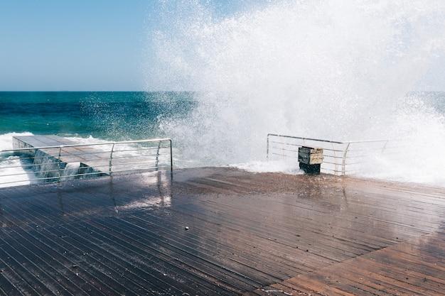 De grosses vagues déferlent sur le quai