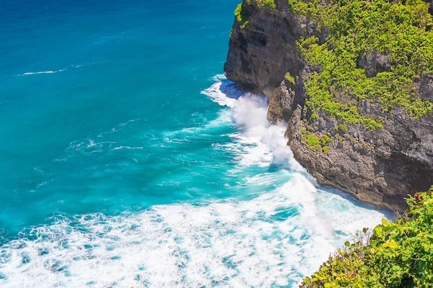 De grosses vagues se brisent sur une côte rocheuse bali indonésie