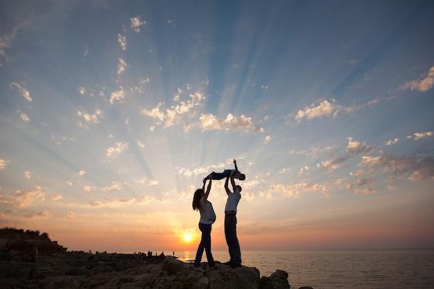 Grossesse et famille heureuse. la femme enceinte avec son mari et son enfant se tenant la main marchant sur le coucher du soleil sur la mer