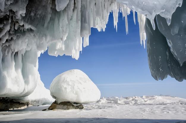 Grotte de glace blanche bleue avec stalactites de glaçons, ciel bleu et glace couverte de pierre