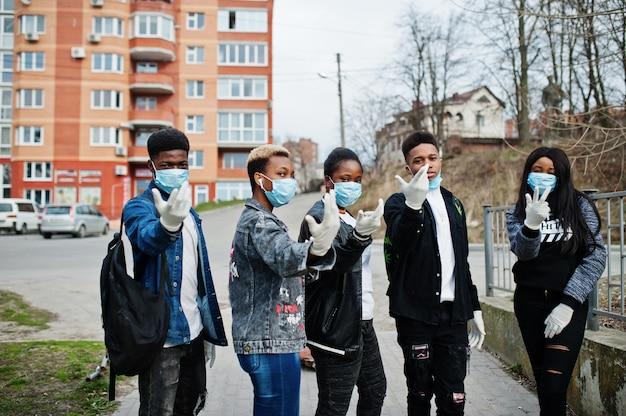 Groupe d'adolescents africains amis contre rue vide avec bâtiment portant des masques médicaux protègent contre les infections et les maladies du virus coronavirus en quarantaine.