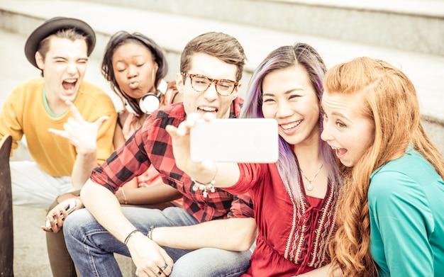 Groupe d'adolescents assis sur les escaliers et prenant selfie