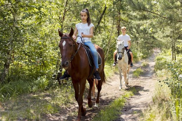 Groupe d'adolescents à cheval dans le parc d'été