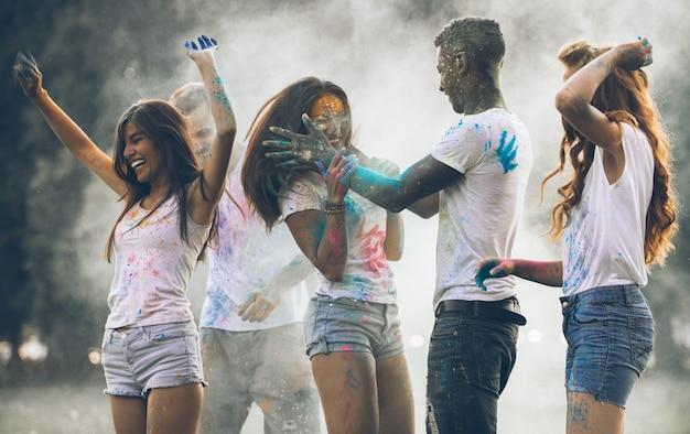 Groupe d'adolescents jouant avec des couleurs au festival de holi, dans un parc
