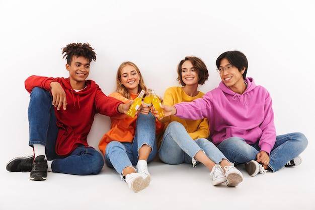 Groupe d'adolescents joyeux isolés, grillage avec des boissons gazeuses