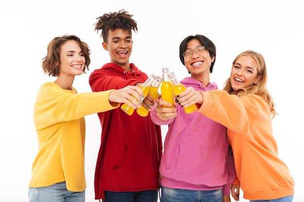 Groupe d'adolescents joyeux isolés, grillage avec des bouteilles de boissons gazeuses