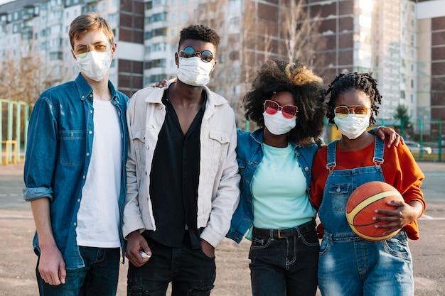 Groupe d'adolescents posant avec des masques médicaux