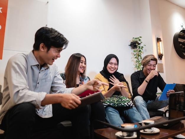 Groupe d'adolescents souriants restant ensemble lors de l'affectation de travail ensemble à l'aide de gadget
